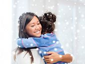 childhood, happiness, family and people concept - smiling little girl and mother hugging indoors