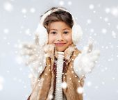 winter, people, childhood and happiness concept - happy little girl in winter clothes