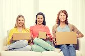 transportation, post and friendship concept - three smiling teenage girls with cardboard boxes at home