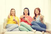 friendship, technology and internet concept - three smiling teenage girls with smartphones at home showing thumbs up
