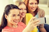 friendship, technology and internet concept - three smiling teenage girls taking picture with smartphone camera at home
