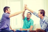 teamwork, friendship and happiness concept - smiling male friends giving high five at home