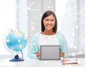 education, winter, technology and people concept - smiling young woman with globe and notebooks showing blank tablet pc computer screen indoors