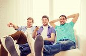 friendship, technology and home concept - smiling male friends with remote control at home
