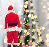 christmas, holidays and people concept - man in costume of santa claus from back over tree lights background