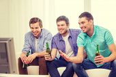friendship, sports and entertainment concept - happy male friends with beer watching tv at home
