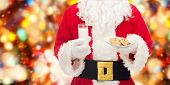 christmas, holidays, food, drink and people concept -close up of santa claus with glass of milk and cookies over red lights background