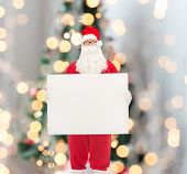holidays, advertisement and people concept - man in costume of santa claus with white blank billboard over christmas tree lights background