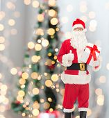christmas, holidays and people concept - man in costume of santa claus with gift box showing thumbs up gesture over tree lights background