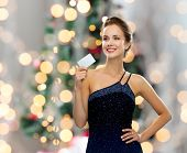 shopping, wealth, holidays and people concept  - smiling woman in evening dress holding credit card over christmas tree lights background