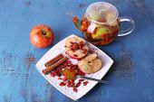 Ripe apple, honey in spoon, goji berries and cinnamon on white square plate and fruit drink in glass teapot on blue wooden background