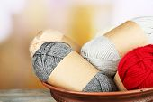 Knitting yarn on wooden table, on light background