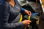 picture of sewing  - Middle aged woman sewing in a sewing workshop - JPG