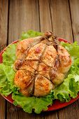 pic of bondage  - Bondage shibari roasted chicken with salad leaves on red plate on wooden background with space vertical - JPG
