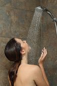 stock photo of jet  - Woman enjoying the water in the shower under a water jet - JPG