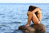 stock photo of lonely woman  - Lonely worried woman sitting on a rock on the beach in the middle of the ocean - JPG