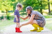 stock photo of little young child children girl toddler  - Young mother and little adorable child girl in rubber boots having fun together family look in summer park on sunny warm day - JPG