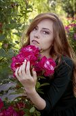 stock photo of auburn  - Beautiful young woman with auburn hair and green eyes admiring roses in the rosary - JPG