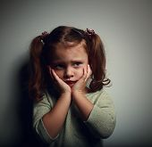 stock photo of horror  - Abandoned scared kid with hands near face looking with horror on dark background - JPG