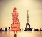stock photo of redhead  - Redhead girl with suitcase on Eiffel tower background - JPG