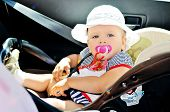 stock photo of seatbelt  - cute baby girl is sitting in car seat - JPG