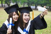 stock photo of two women taking cell phone  - Two happy women in graduation gowns taking picture with cell phone - JPG