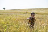 stock photo of tall grass  - Little girl walks through tall autumn grass - JPG