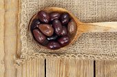 pic of ladle  - brown olives in wooden ladle on burlap texture - JPG