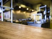 stock photo of kitchen appliance  - Top of Wooden Table Counter with Blurred Kitchen Restaurant Background - JPG