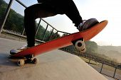 picture of skateboarding  - young skateboarder legs skateboarding at skatepark ramp - JPG