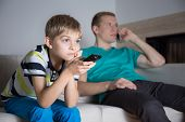 stock photo of boring  - Little bored boy watching movie in living room - JPG