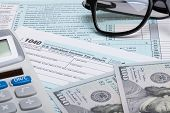 image of irs  - US 1040 Tax Form calculator glasses and dollars  - JPG