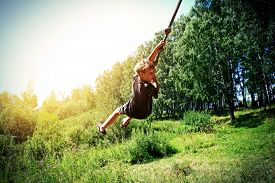 image of jumping  - Vignetting Photo of Kid Bungee jumping in the Summer Forest - JPG