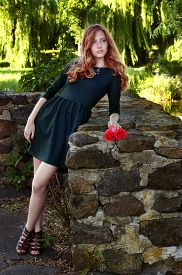 stock photo of auburn  - Young woman with auburn hair in the swamps posing with red flowers - JPG