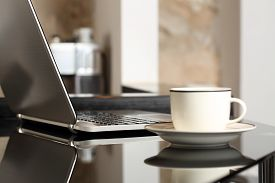 pic of self-employment  - Laptop on a table workplace with a cup of coffee in a home interior or office - JPG