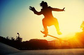 pic of skateboard  - young skateboarder practice skateboarding trick ollie at skatepark - JPG