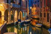 picture of dock  - Lateral canal and pedestrian bridge in Venice at night with street light illuminating bridge and houses - JPG