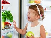 picture of healthy eating girl  - little girl child is crying and acting about fridge with healthy eating fruit - JPG