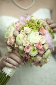 stock photo of purple rose  - Bride in white dress holding beautiful fresh wedding bunch of pink lilac purple white and violet chrysanthemum rose and peony flowers in hand closeup vertical picture - JPG
