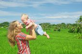 stock photo of mother baby nature  - Happy mother tossing up joyful baby boy on Balinese green rice terraces background - JPG
