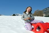 stock photo of sled  - pretty enjoyed girl plays with red sled in the mountains in the snow - JPG