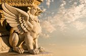 image of stone sculpture  - Stone sculpture of a gargoyle at the sunset - JPG