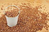 stock photo of buckwheat  - White bucket of buckwheat on the wooden floor as a background - JPG