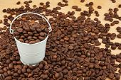 stock photo of bucket  - White bucket with coffee beans on the wooden floor as a background - JPG