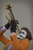 stock photo of clown face  - Professional trumpet player with face painted as human skull - JPG