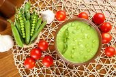 stock photo of vegetable soup  - Tasty peas soup and vegetables on table close up - JPG