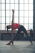 picture of extend  - A strong muscular woman is doing the extended triangle pose in yoga in a city loft gym - JPG