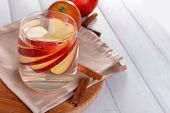 stock photo of cider apples  - Glass of apple cider with fruits and cinnamon on table close up - JPG