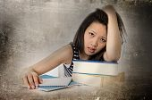 picture of boring  - young pretty chinese asian student woman bored tired and overworked leaning on school books studying for exam in education concept on edgy grunge background - JPG