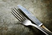 stock photo of knife  - Dining fork and knife on rustic vintage background with copyspace - JPG